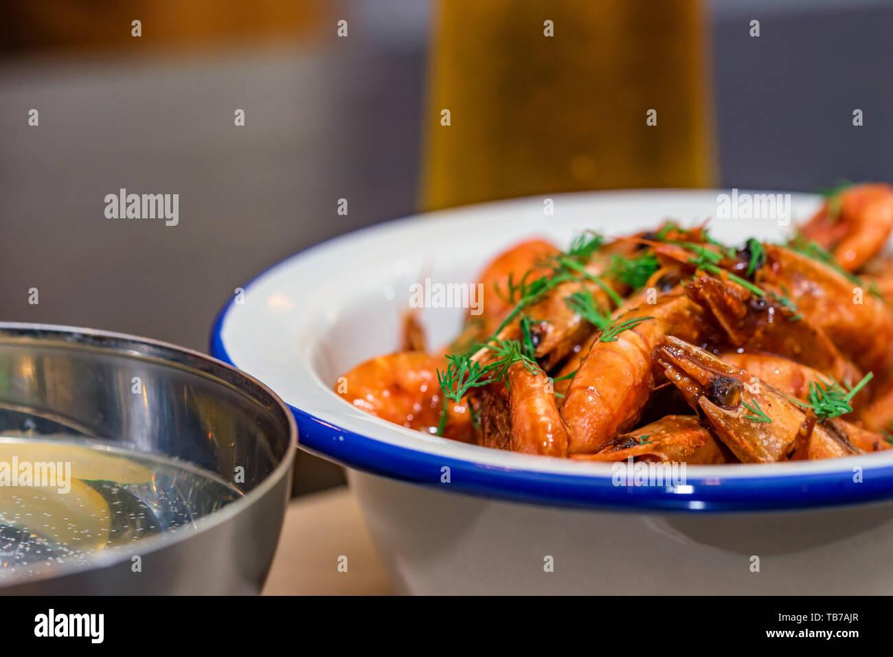 Camarones preparados con eneldo en un recipiente sobre la mesa con dos vasos de cerveza y agua Foto de stock