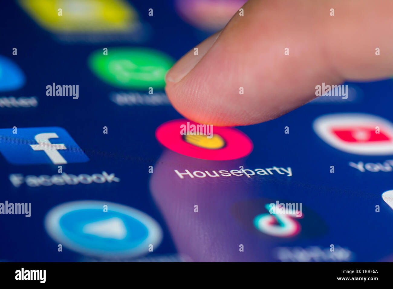 Dedo pulsando un icono de acceso directo en un teléfono inteligente o una tableta táctil para cargar los medios sociales Houseparty app. Aplicación de House Party. Imagen De Stock