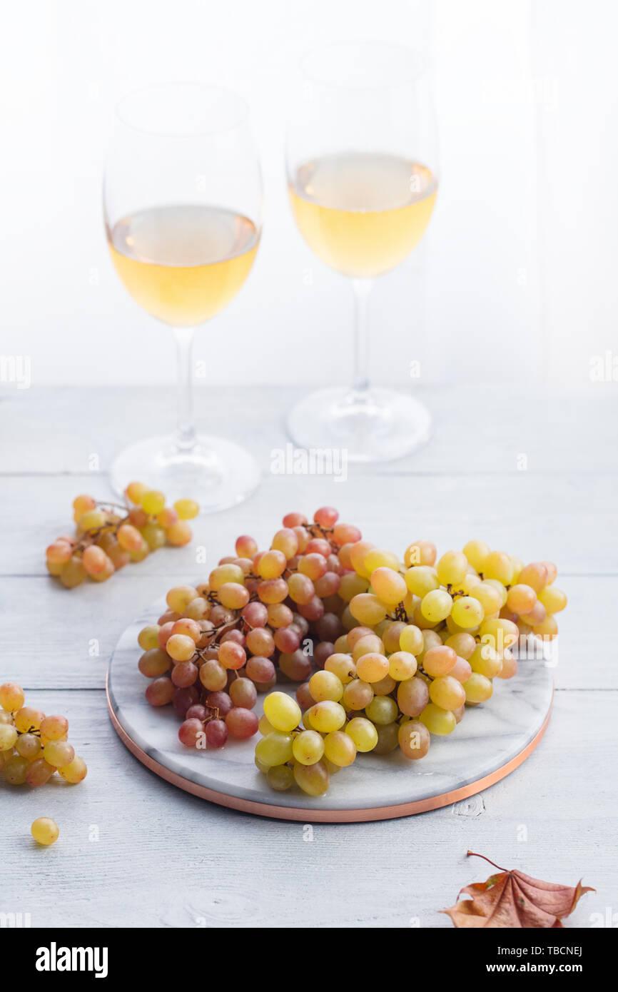 Uva fresca sobre la tabla de cortar mármol con copas de vino blanco. Fondo de madera. Foto de stock