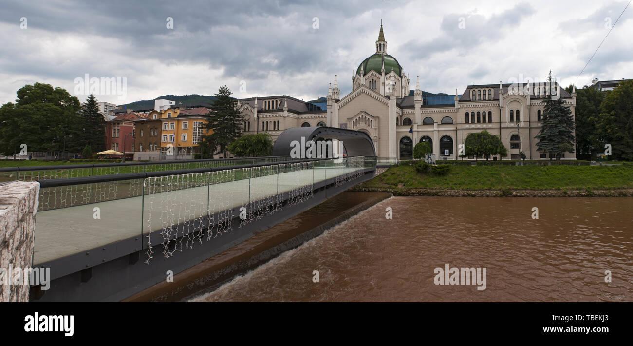 Sarajevo: el Festina lente puente con su repetición en el oriente, a lo largo del río Miljacka, y el palacio de la Academia de Bellas Artes, Universidad pública Foto de stock