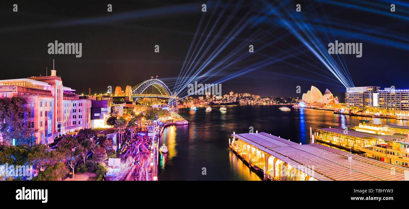 Panorama de Sydney Harbour cerca de Circular Quay y el Puente del Puerto de Sydney durante el Vivid Sydney espectáculo de luz con rayos láser azul dibujar líneas en el ni Foto de stock