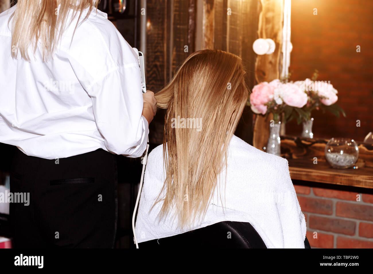 Concepto de belleza y cuidado del cabello. Alegre hermosa mujer rubia vistiendo franela blanca haciendo a su novia peinados con pelo hierro. Foto de stock