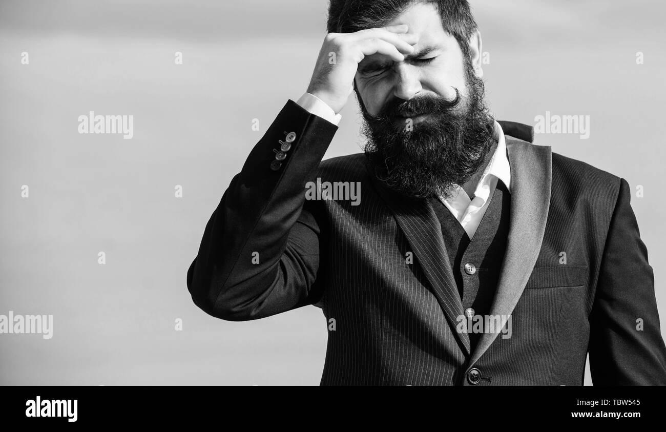 El fracaso de la empresa. El hombre barbado rostro doloroso estresantes de fondo del cielo. Guy sufren cefalea día estresante. Estresante negocio. El dolor y la jaqueca. La frustración y la decepción. Error imperdonable. Imagen De Stock