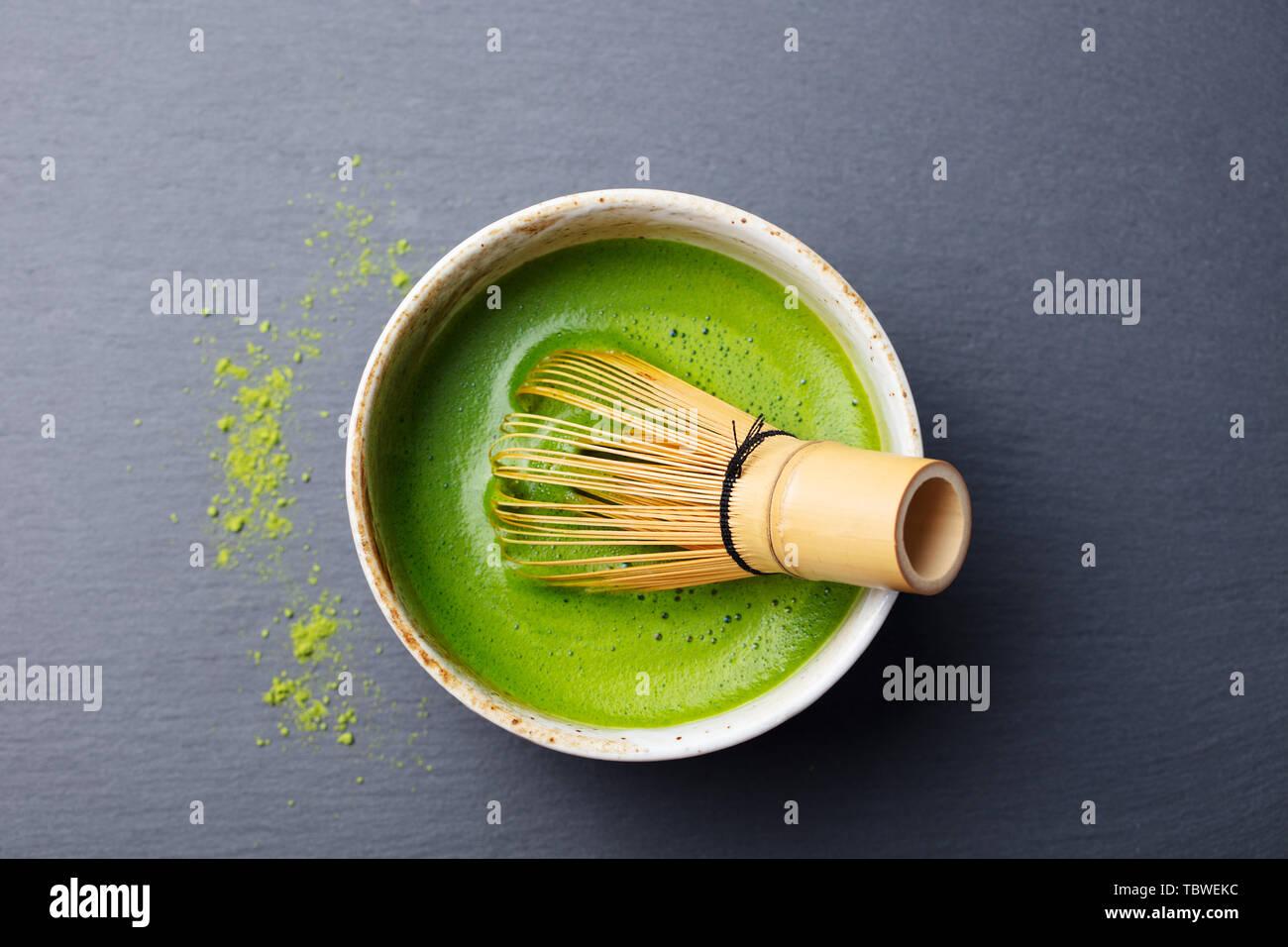 Té verde matcha proceso de cocción en un recipiente con batidor de bambú. Fondo de pizarra negra. Vista desde arriba. Foto de stock