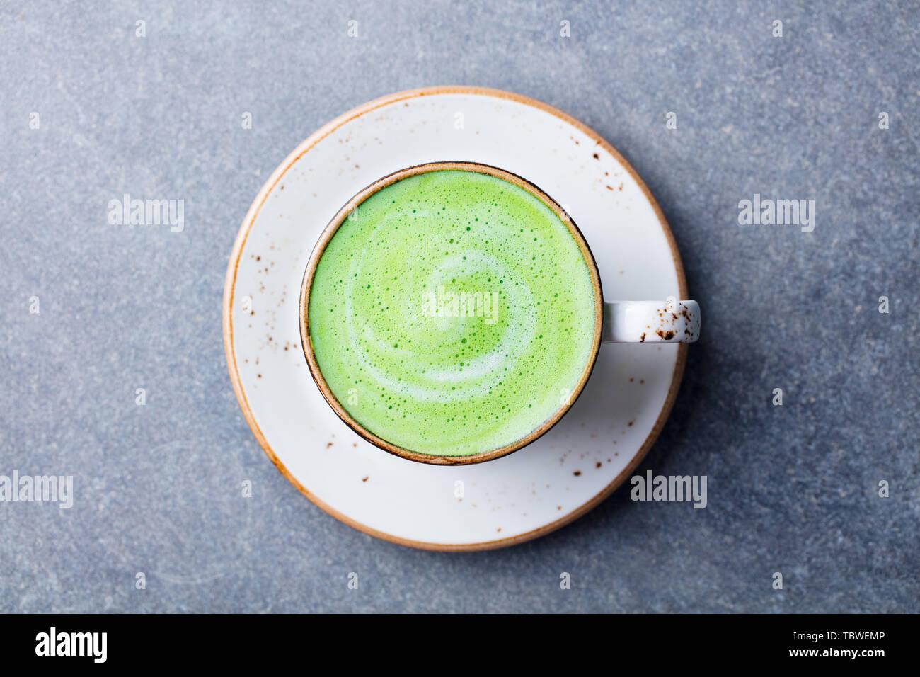 Té verde matcha latte en una copa. Fondo de piedra gris. Vista desde arriba. Foto de stock