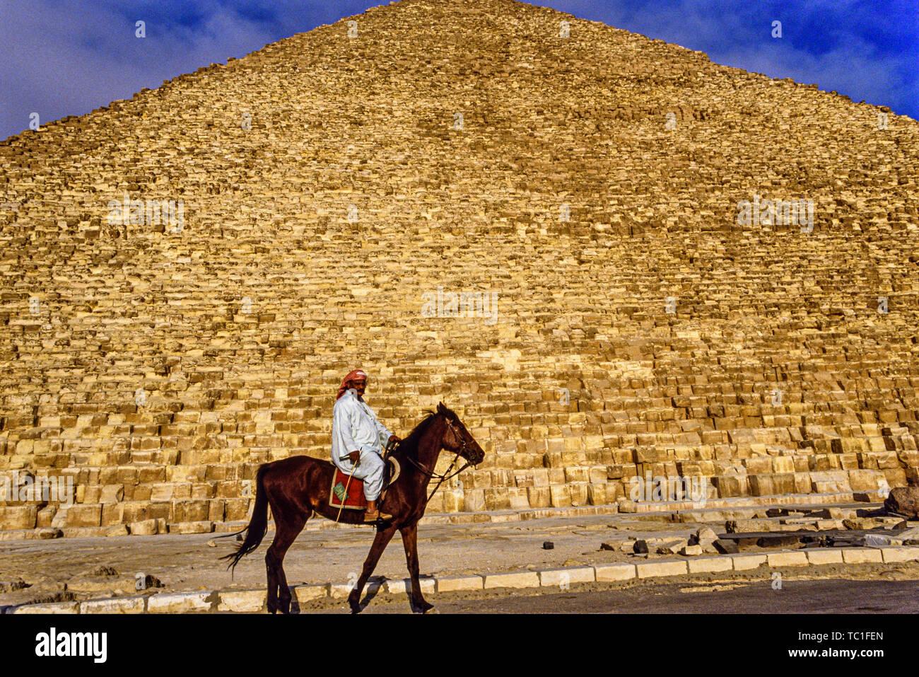 Foto: © Simon Grosset. La Pirámide de Giza, complejos o necrópolis de Giza, cerca de El Cairo, Egipto. Un hombre monta un caballo delante de la Gran Pirámide de Giza, oh Foto de stock