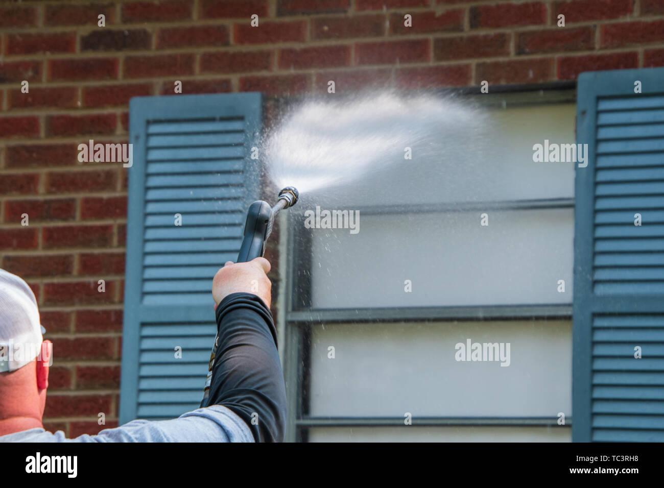 Brazo y mano sujetando una pulverizadora encaminadas a una ventana que tiene un obturador azul sobre una pared de ladrillo rojo. La boquilla está pulverizando una amplia agua en la ventana Imagen De Stock