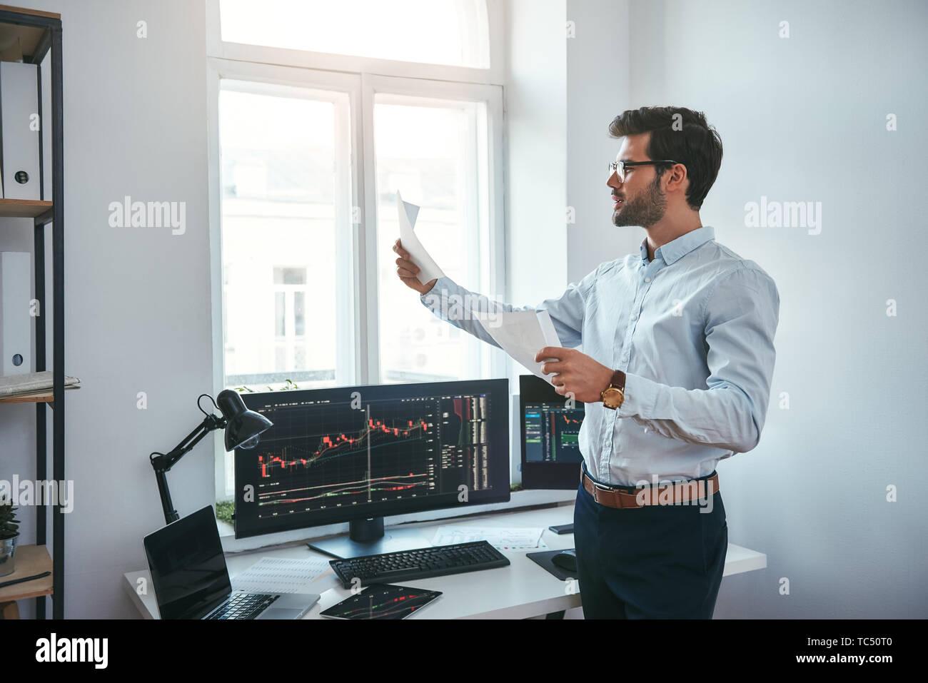 Estrategia de trading. Inteligente y joven comerciante en anteojos mirando informes financieros y analizar gráficos comerciales mientras está de pie delante de las pantallas de las computadoras en la oficina moderna. Corredor de bolsa. El mercado Forex. Concepto de comercio Foto de stock