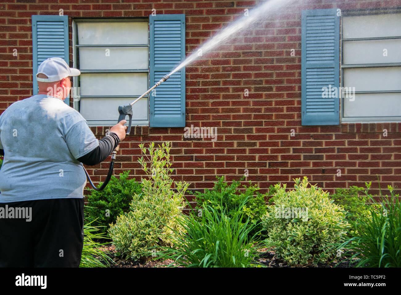 Pesado caucásica sobrepeso hombre rociado de agua desde una boquilla en los ladrillos y las persianas de una casa. Hay arbustos y plantas en frente de él. Sombras Imagen De Stock