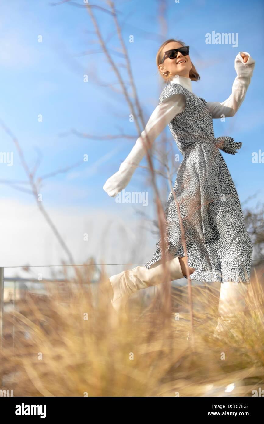 Exuberante blogger de moda mujer corriendo hacia delante, en Múnich, Baviera, Alemania. Imagen De Stock