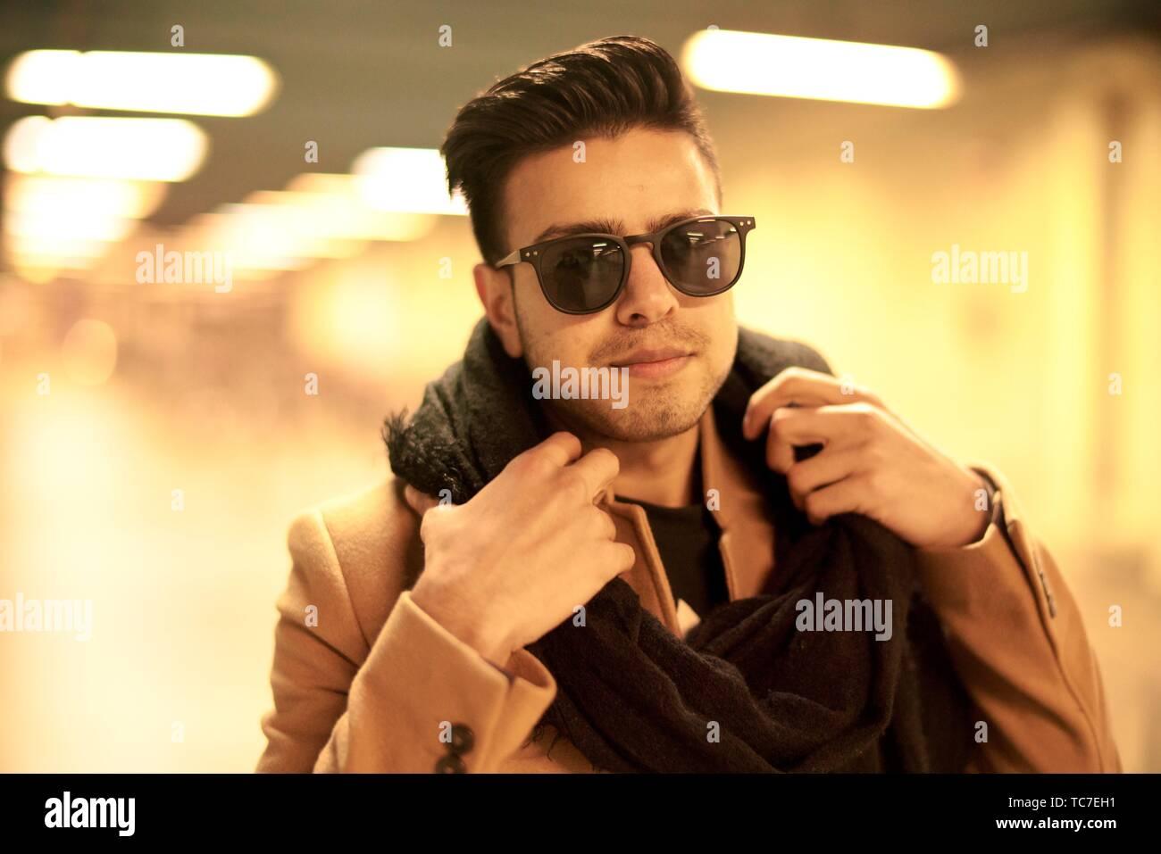 5a8864fa5 Moda joven hombre con bufanda y gafas de sol en interiores en subterráneo  en Munich,