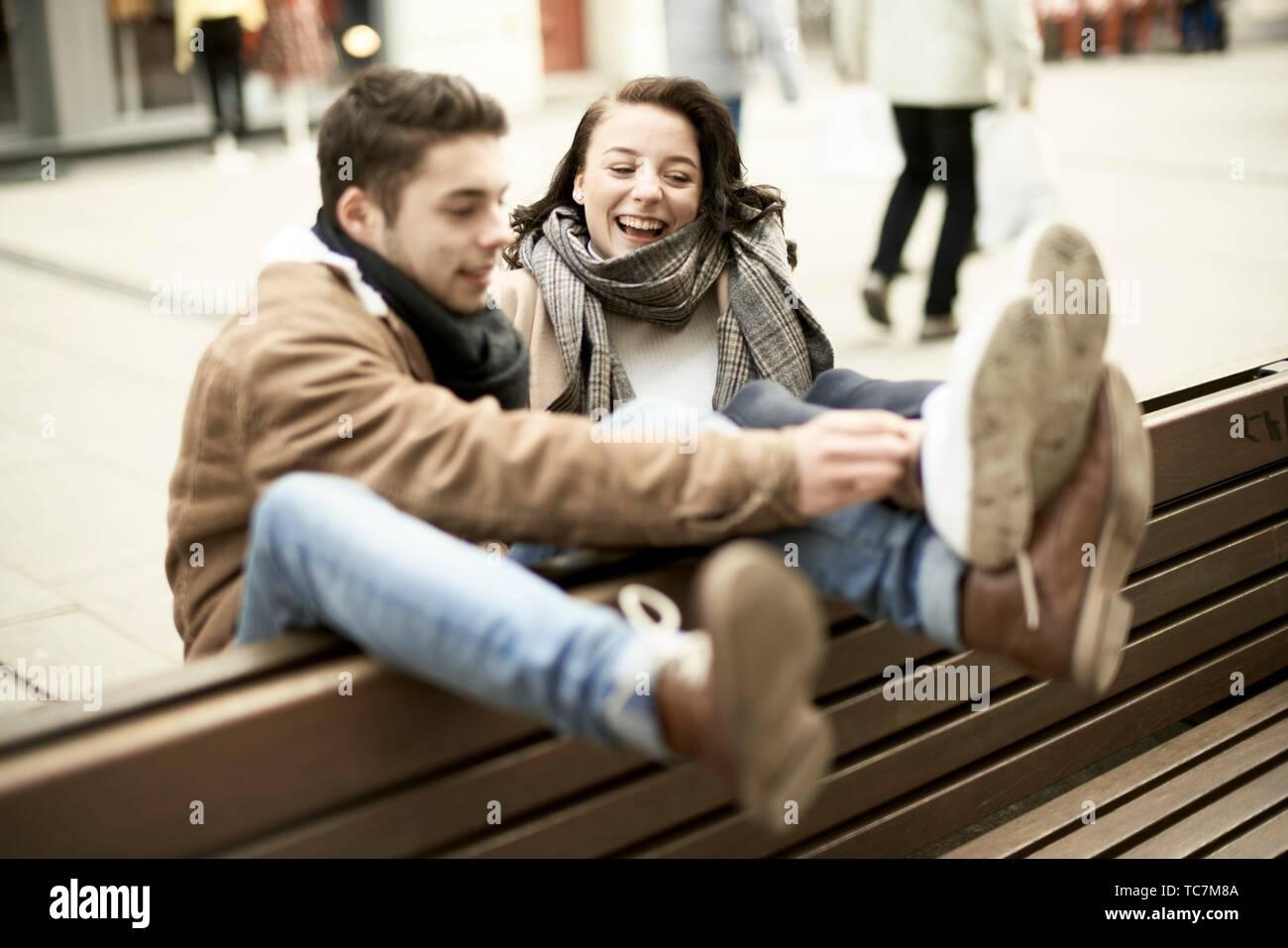 La pareja de adolescentes jóvenes sentados en un banco al revés en ciudad, colgando juntos, patas arriba, boca abajo, en Cottbus, Brandenburgo, Alemania Foto de stock