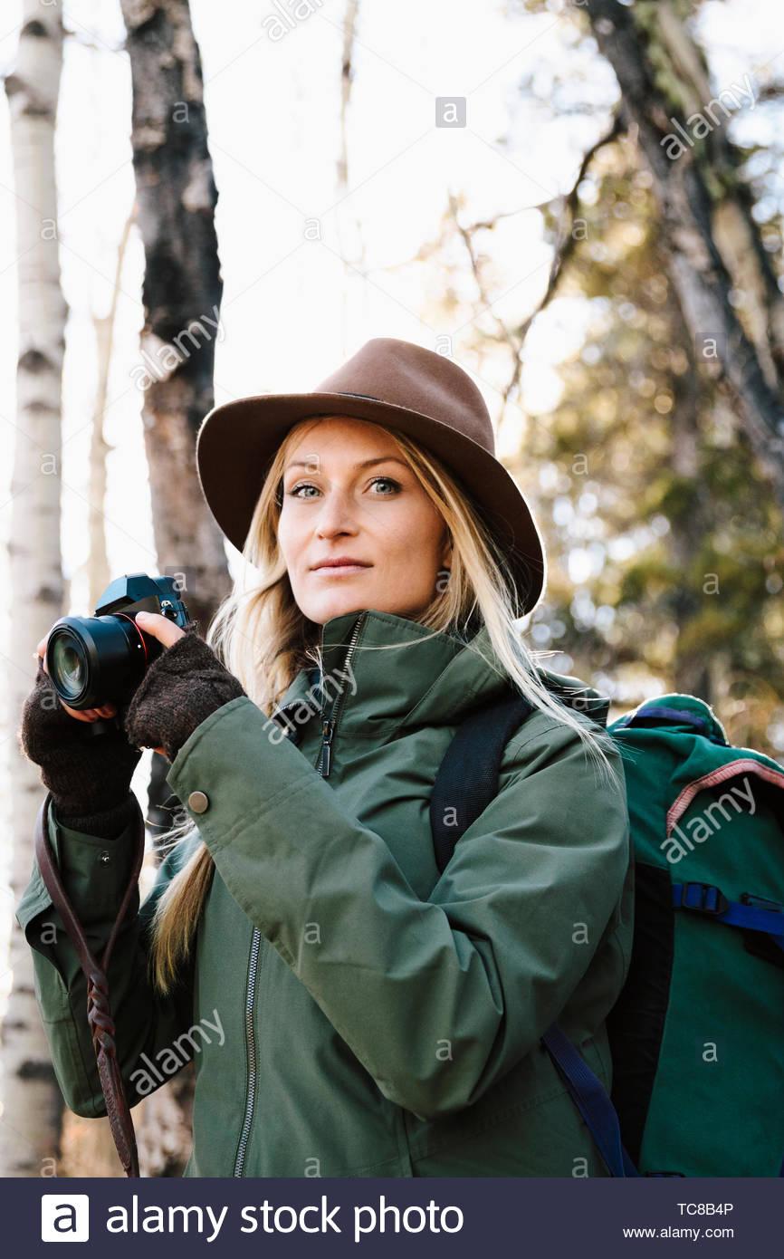 Retrato mujer confiada con mochila y cámara senderismo Imagen De Stock