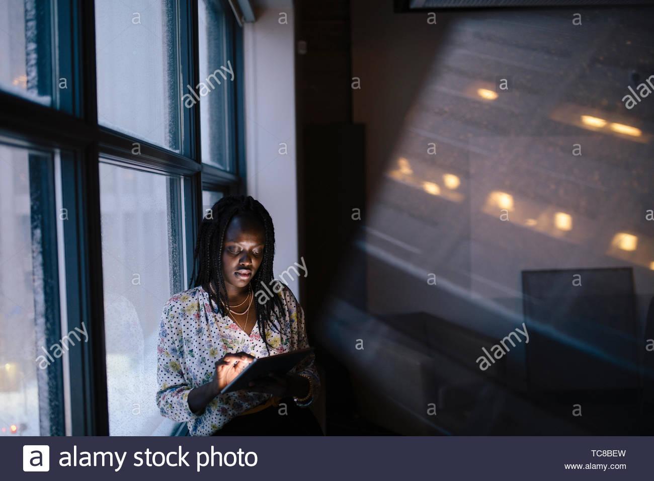 Empresaria dedicada trabajando tarde en tableta digital en la ventana de la oficina oscura Imagen De Stock