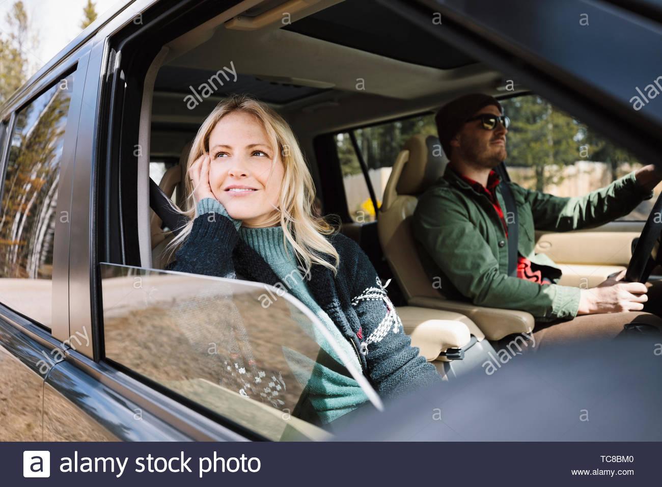 Mujer serena cabalgatas en SUV, disfrutando de Road Trip. Imagen De Stock