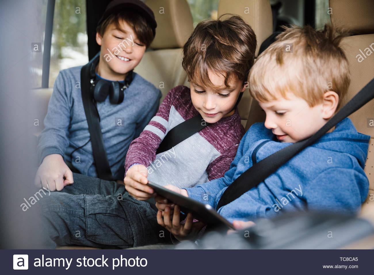 Hermanos utilizando digital comprimido en el asiento de atrás del coche Imagen De Stock