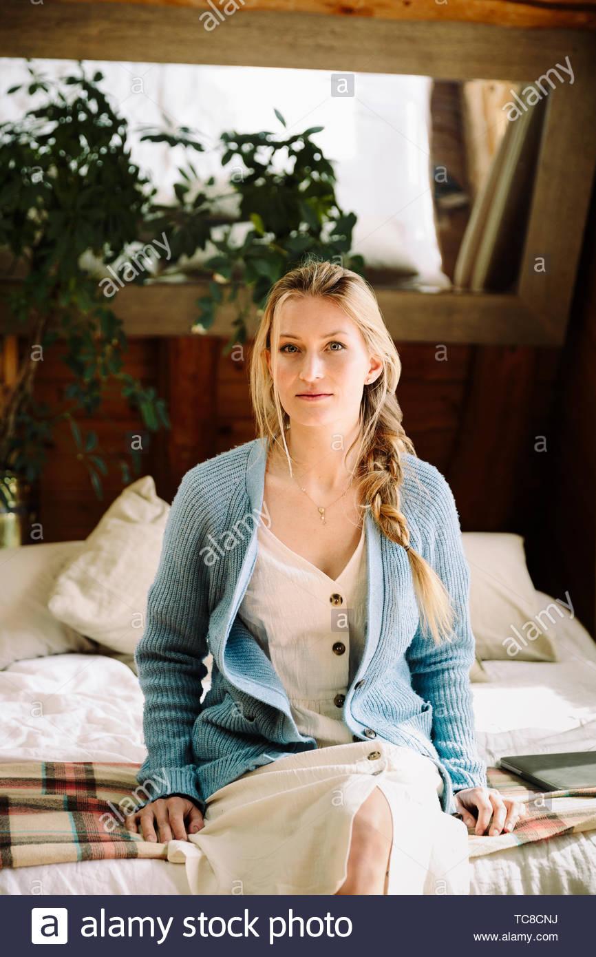Seguro retrato Mujer sentada en el borde de la cama Imagen De Stock