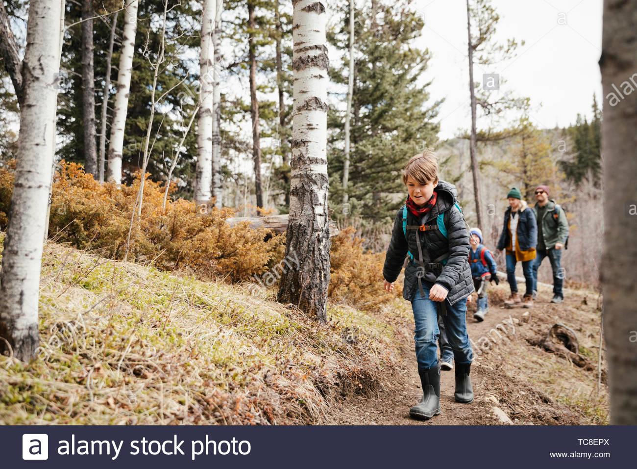 Chico despreocupado senderismo con familia en woods Imagen De Stock