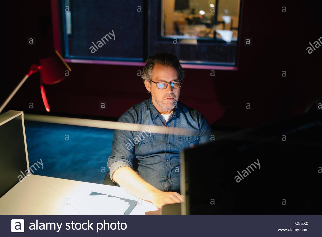 Empresario dedicado trabajando tarde por ordenador en la oscuridad de la oficina Imagen De Stock