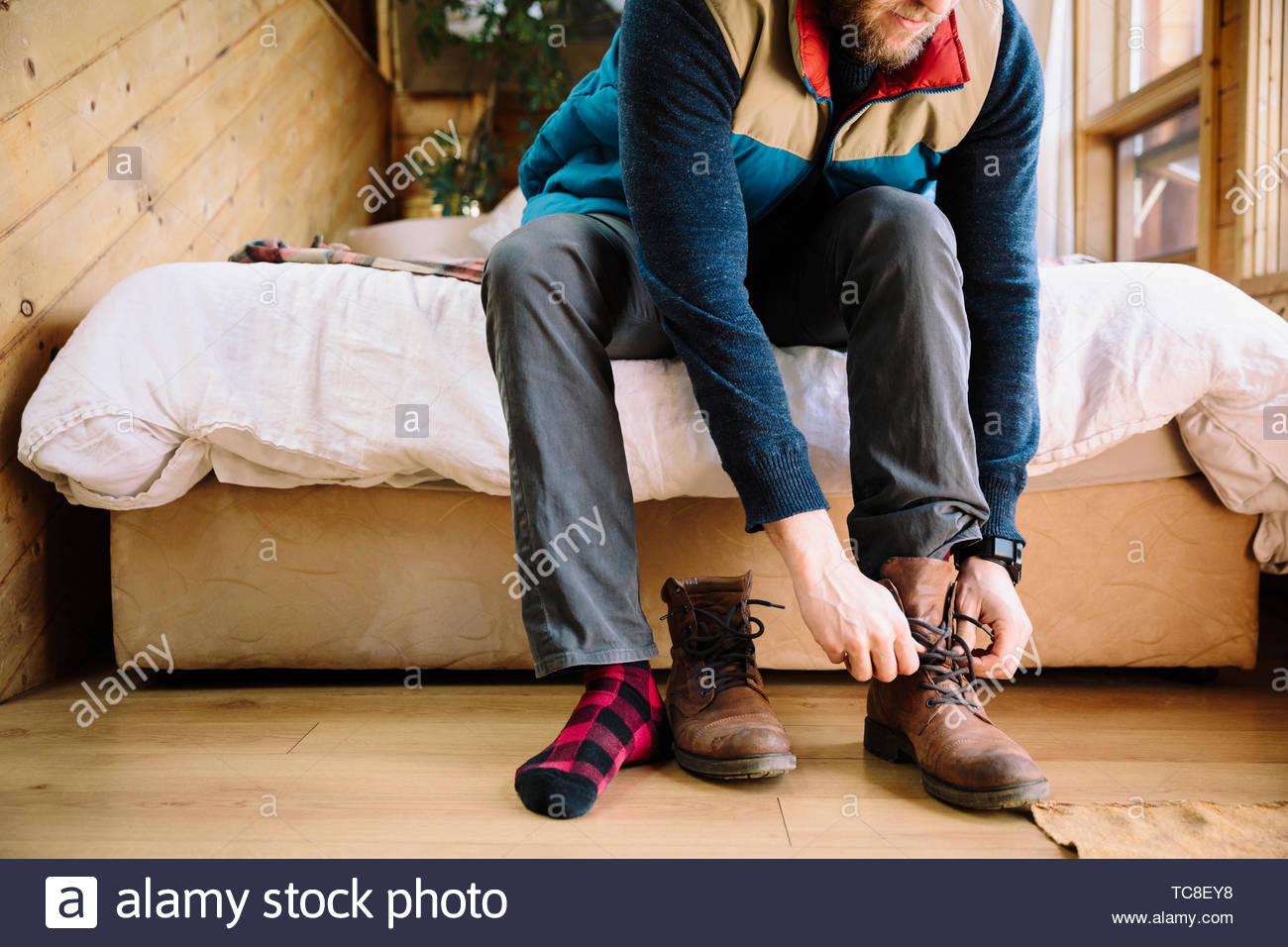 Hombre haciendo las botas en el borde de la cama de la cabina Imagen De Stock