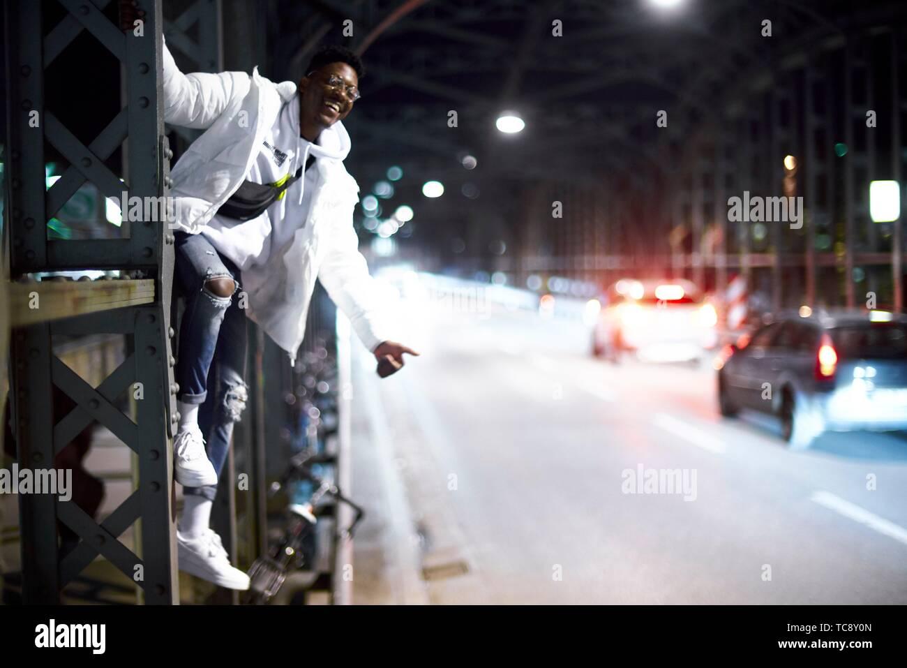 Loco joven gracioso hombre tratando de autostop, colgando sobre metal construcción de puente, Hacker Haccurbrücke bridge, en la noche en la ciudad, al lado de la calle, en Foto de stock
