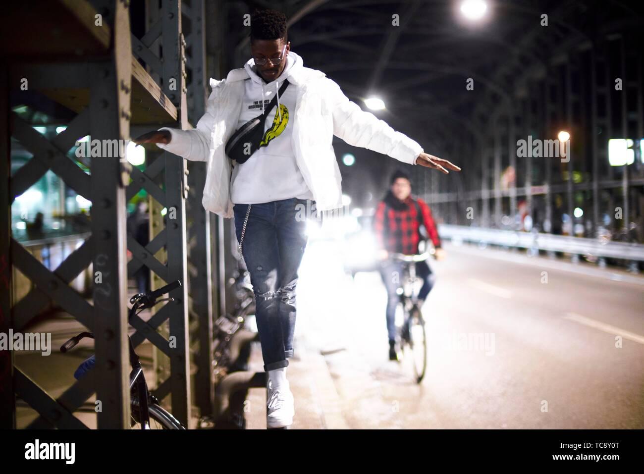Joven equilibrio sobre construcción de puente de metal, Hacker Haccurbrücke bridge, en la noche en la ciudad, junto a la calle, conductor de bicicletas, en Munich, Alemania. Foto de stock