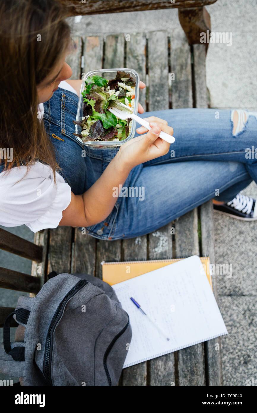 Sección media retrato de un estudiante joven sentada en un banco mientras come sano con ensalada de pasta en una fiambrera de vidrio Foto de stock