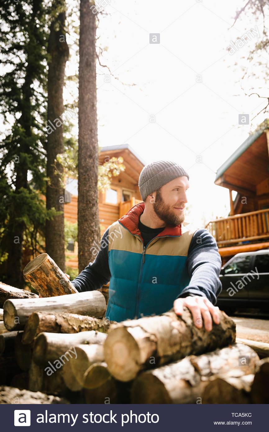 El Hombre recogiendo leña fuera soleado cabaña Imagen De Stock
