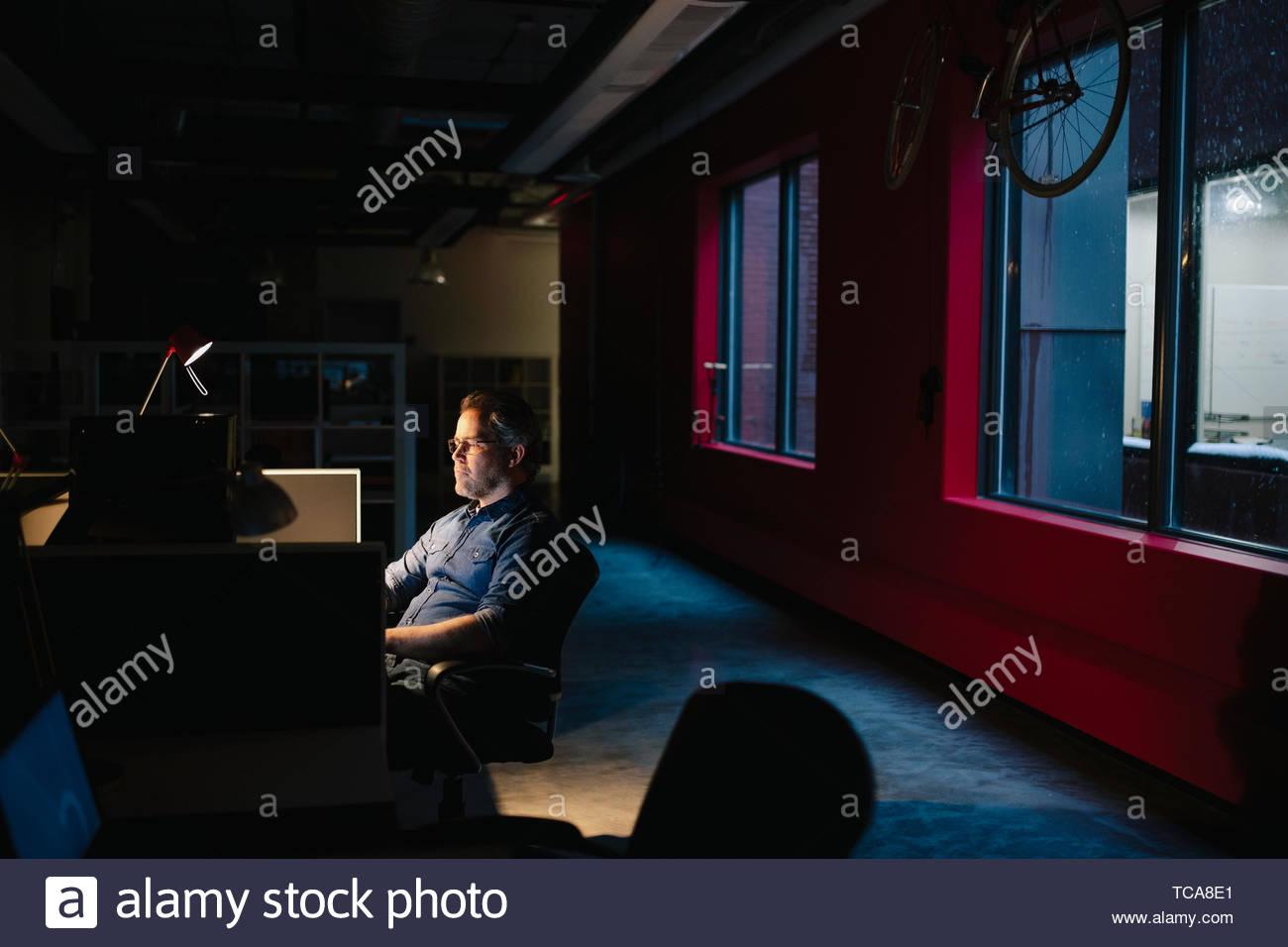 Empresario dedicado trabajando tarde en la oficina oscura Imagen De Stock