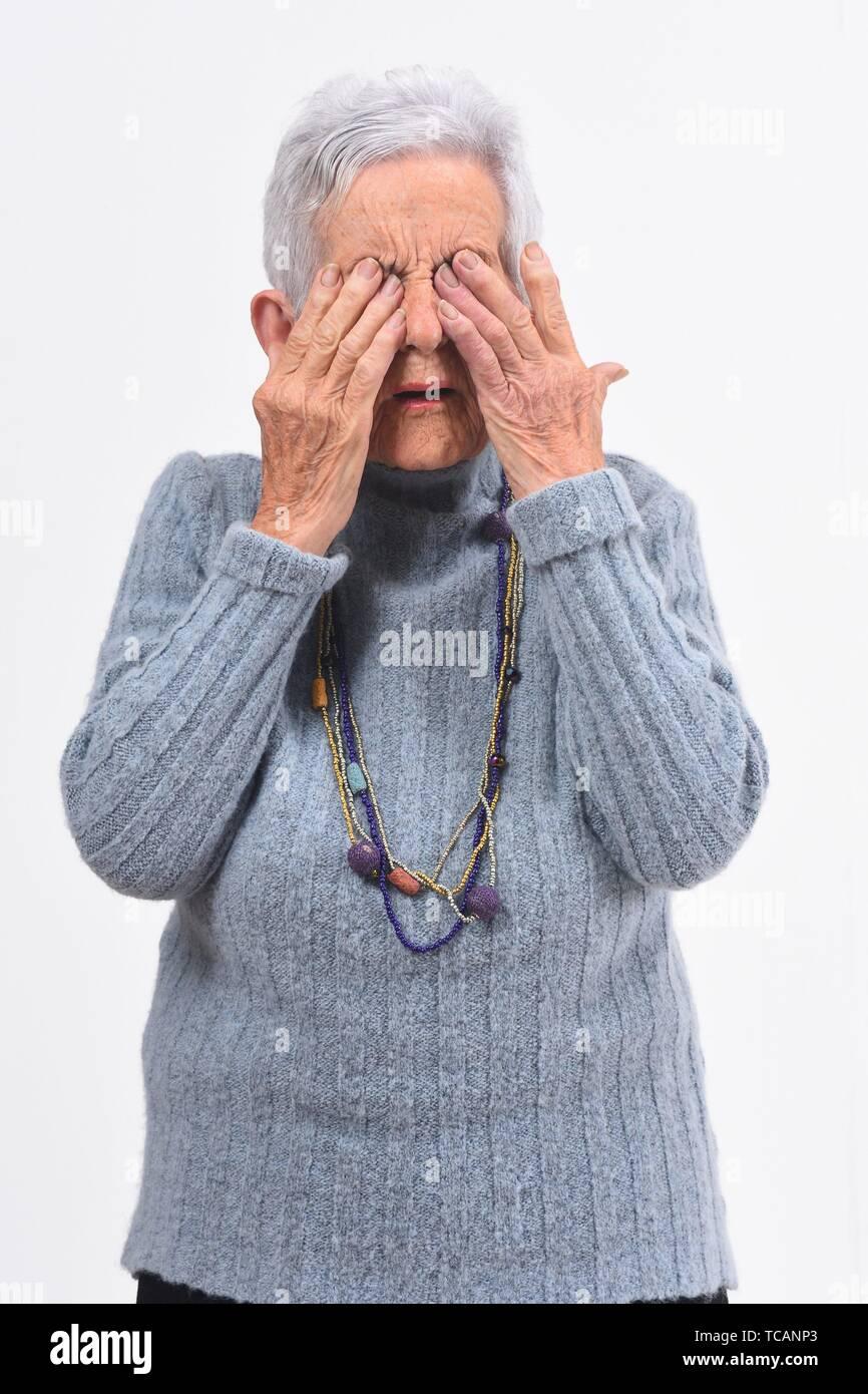 Mujer de edad tener los ojos duelen sobre fondo blanco. Imagen De Stock