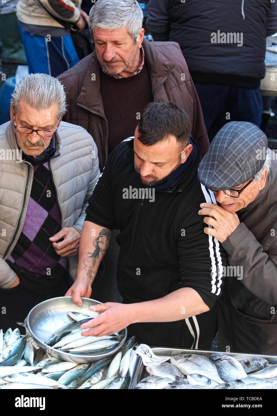 En Catania, Sicilia, Italia - 10 Abr 2019: Pescadería, la venta de pescado fresco en el tradicional mercado de pescado. Hombre mayor, exigente, le está tocando y dar instrucciones. Escena del mercado típico italiano. Foto de stock
