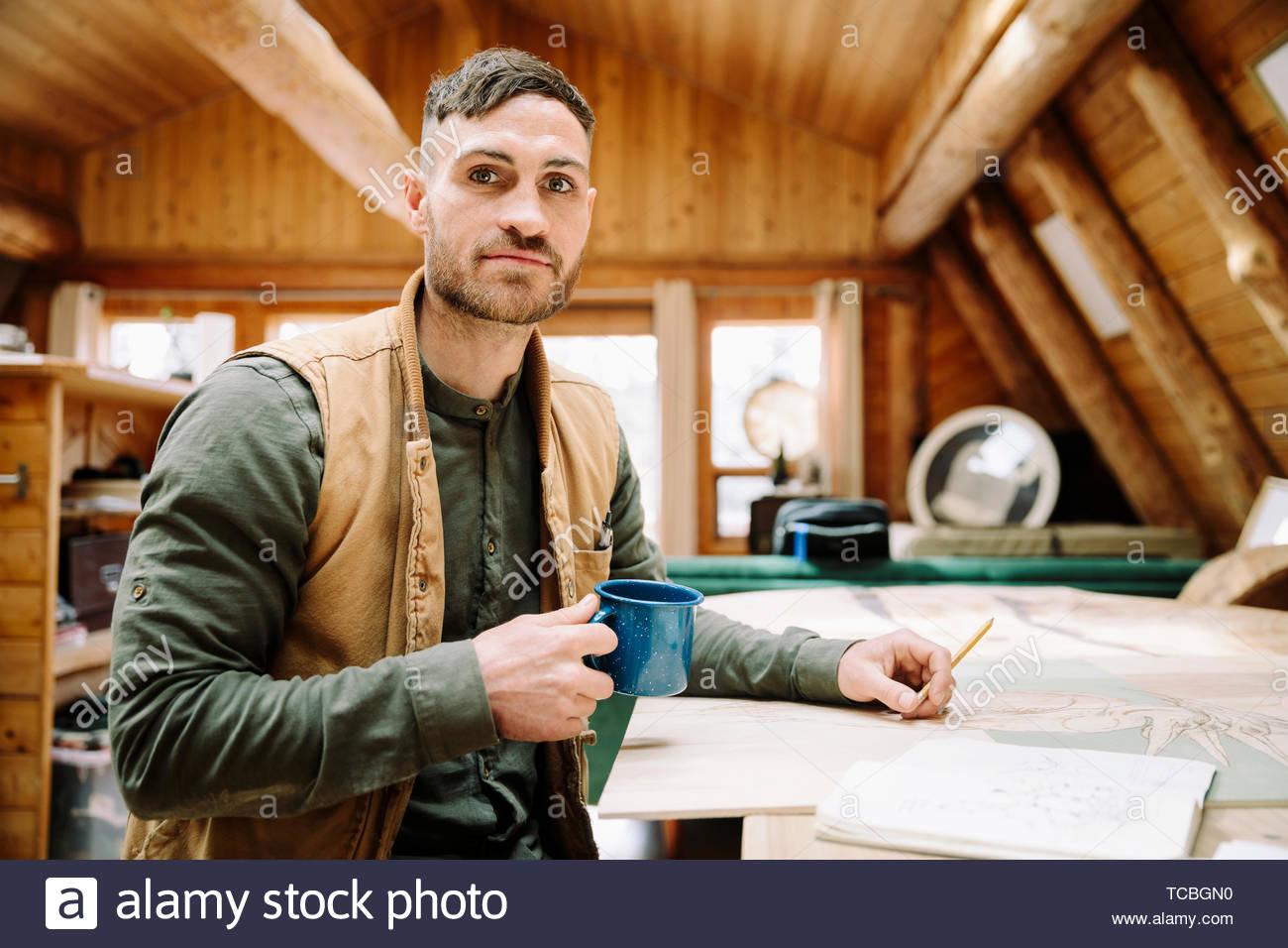 Retrato de dibujo y artista masculino seguro beber café en la mesa de cabina Foto de stock
