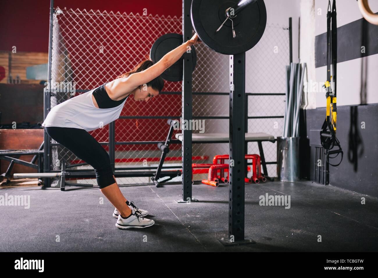 Athletic morena joven haciendo algunos ejercicios de levantamiento de pesas. Foto de stock