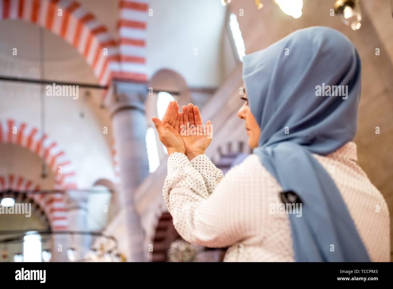 Mujer musulmana en velo hijab y ora con sus manos en el aire con la mezquita de fondo. La religión orando concepto. Foto de stock