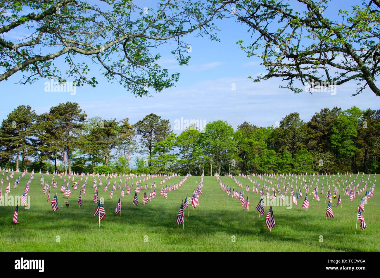 Cementerio Nacional de Bourne, Massachusetts con banderas americanas colocado en cada lápida para Memorial Day enmarcada por ramas de árbol w/ deja Foto de stock