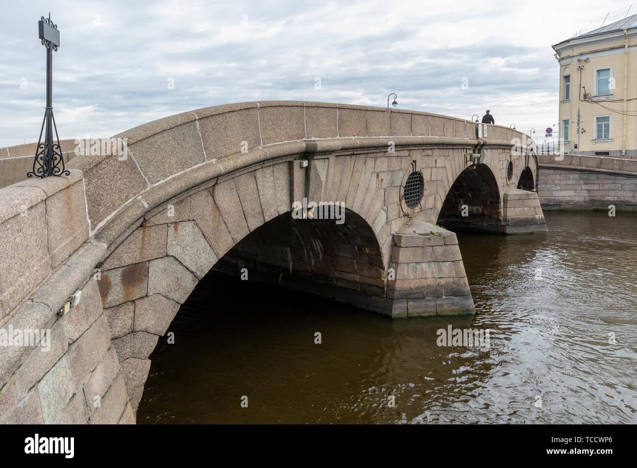 Lone cruce peatonal arco de piedra de puente sobre el río Fontanka en jardín de verano que conecta Palace & Kutuzov terraplenes, San Petersburgo, Rusia Foto de stock