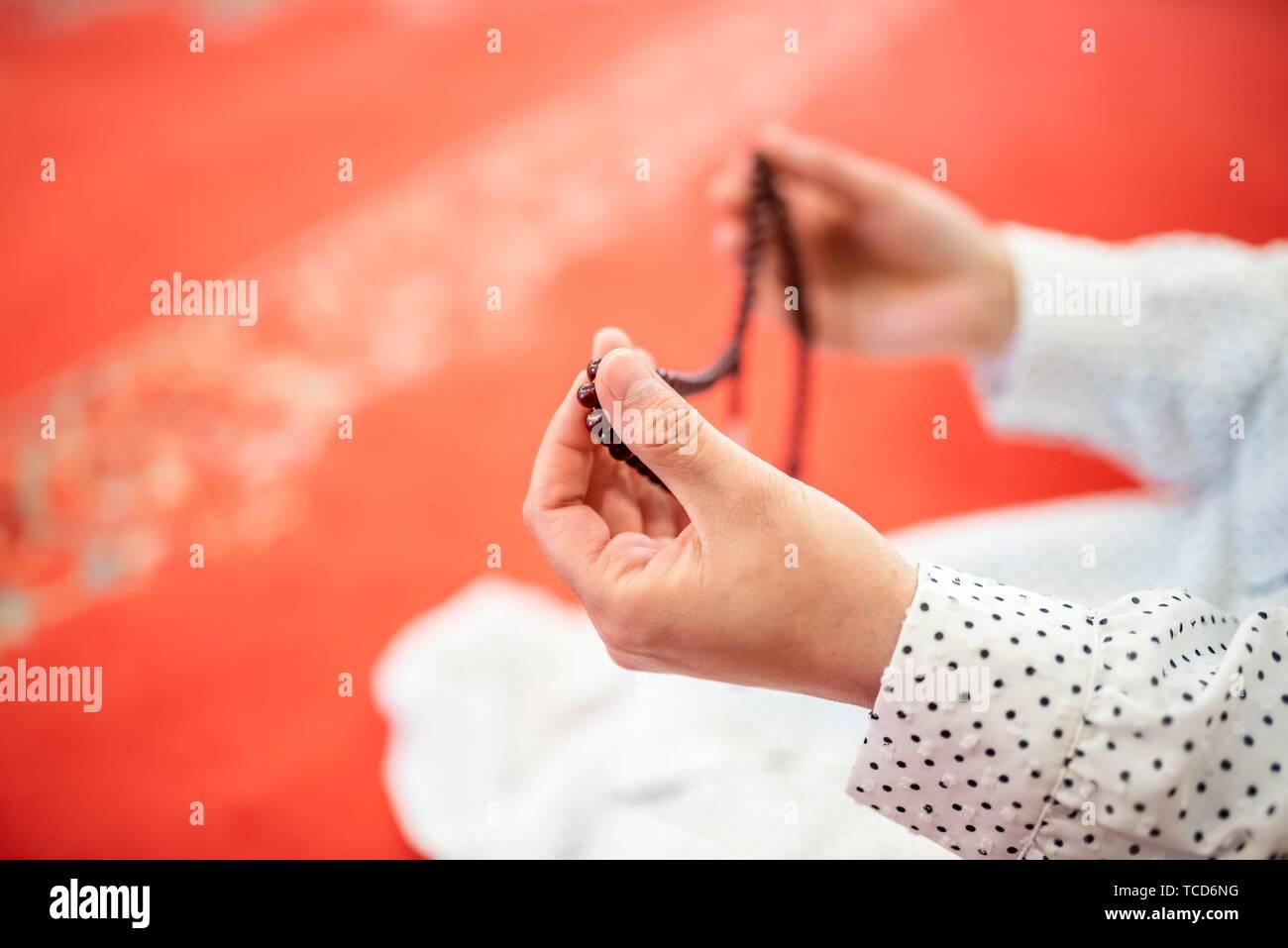 Vista de cerca de una mujer musulmana de manos en el hijab sujetando Rosario con sus manos y orando. La religión orando concepto. Foto de stock