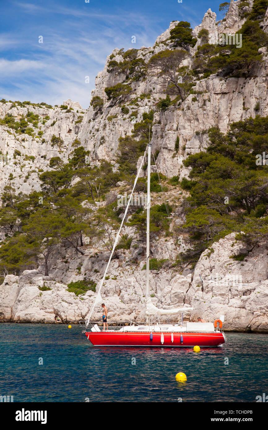 Velero rojo amarrado en uno de los Calanques cerca de Cassis, Provenza Francia Foto de stock