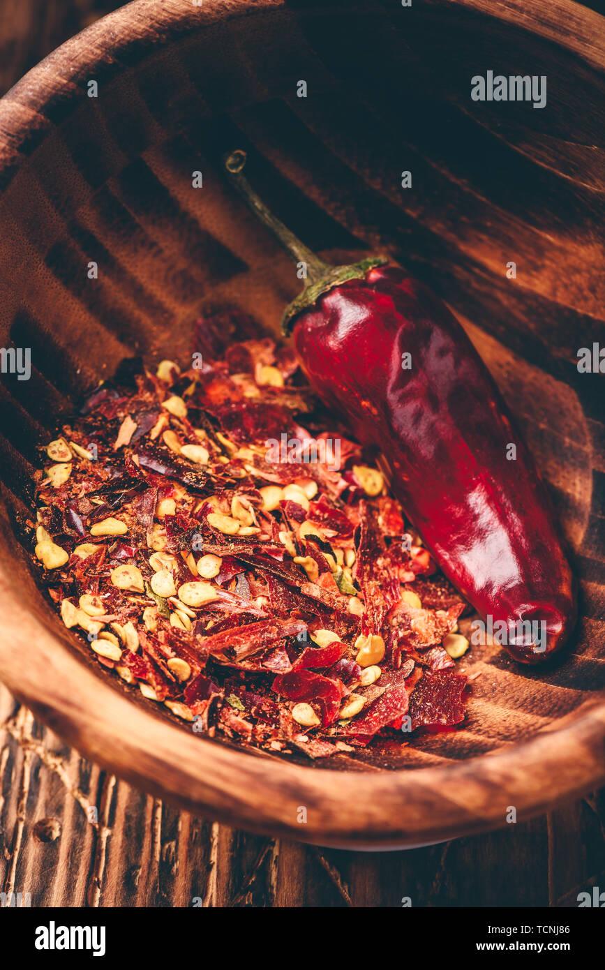Los copos de pimiento rojo de tierra en el tazón de madera Foto de stock