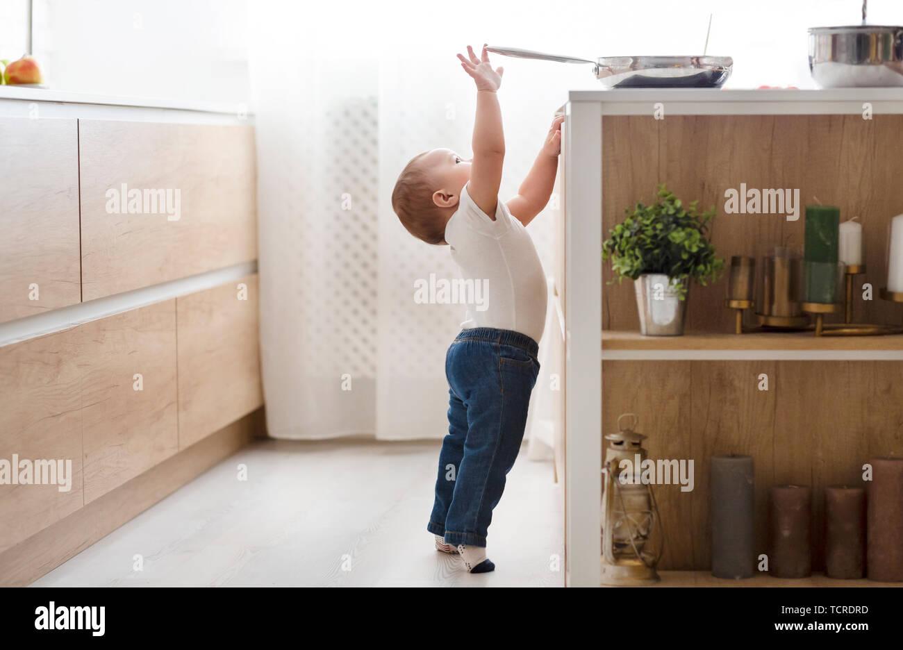 Seguridad infantil en casa concepto - toddler alcanzando por el pan en la estufa en la cocina Foto de stock