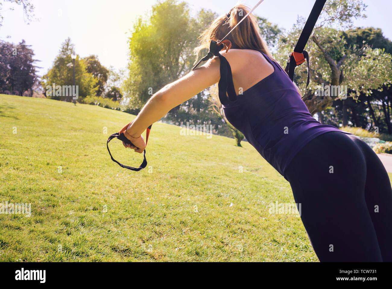 Hermosa joven mujer rubia con tirantes de suspensión, rutina de ejercicios al aire libre, en la noche en un parque soleado Imagen De Stock