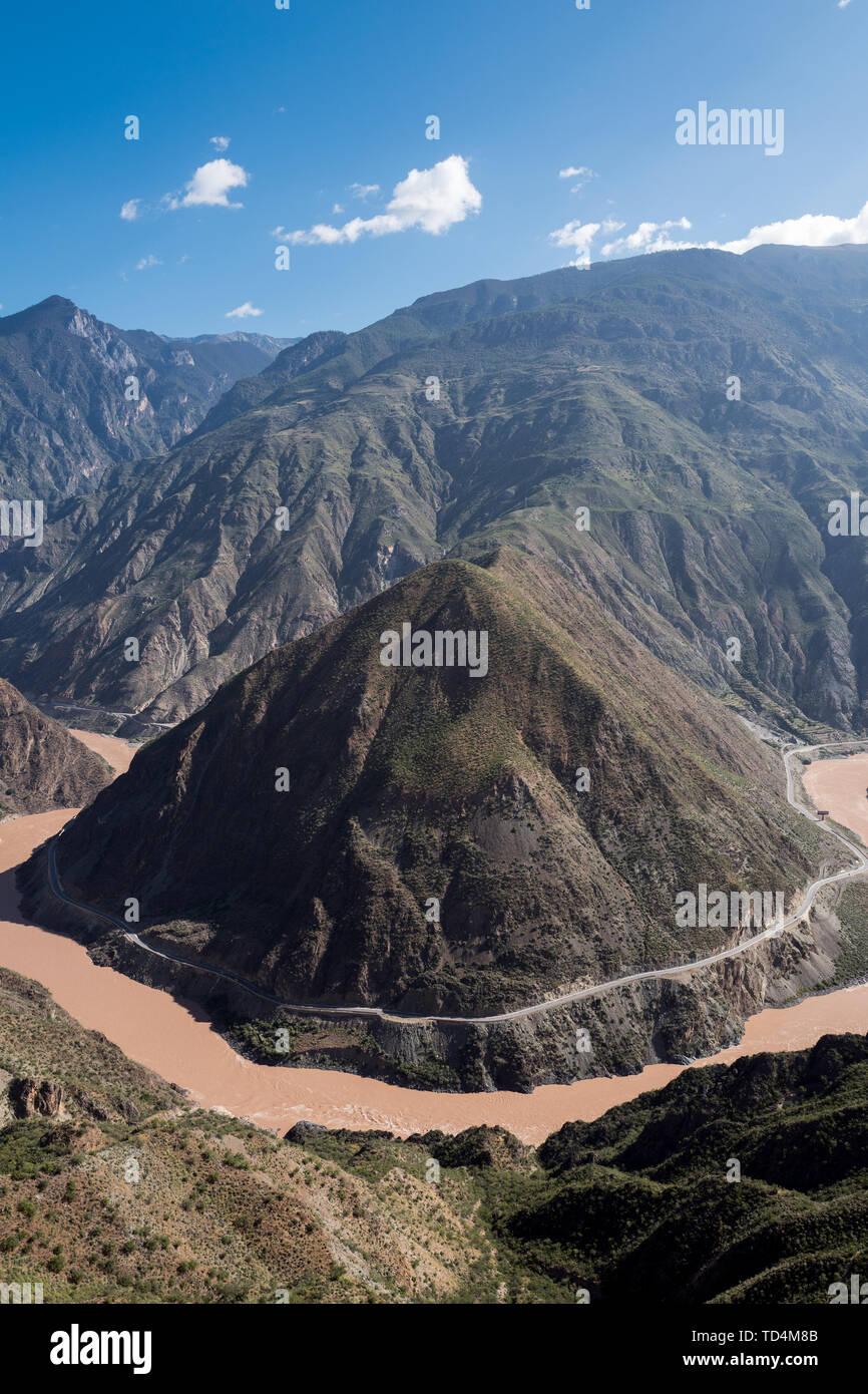 """La primera curva del río Jinsha (como el gran giro del Río Yaruzangbo es también conocida como la curva) a través de la montaña a través del valle del río Jinsha, como consecuencia de ello, la tendencia del agua es aún más vasto, el cañón se abre gradualmente, cuando va a salir de esta fortaleza Sichuan-Yunnan parece querer aliviar la fatiga de la larga distancia ejecuta en primer lugar, por lo que ralentiza y bellamente dibuja un gallardo alrededor de la pirámide-como el Día Pico de cono """" Omega """" un gran cambio en la forma. Inesperadamente, este involuntario ha logrado un espectáculo de improvisación. Foto de stock"""