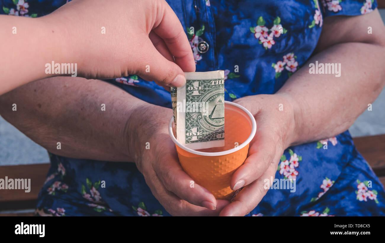 Anciana suplica para limosnas. Primer plano de dinero y de monedas en la mano de la pobre mujer. Los problemas sociales de la sociedad Foto de stock