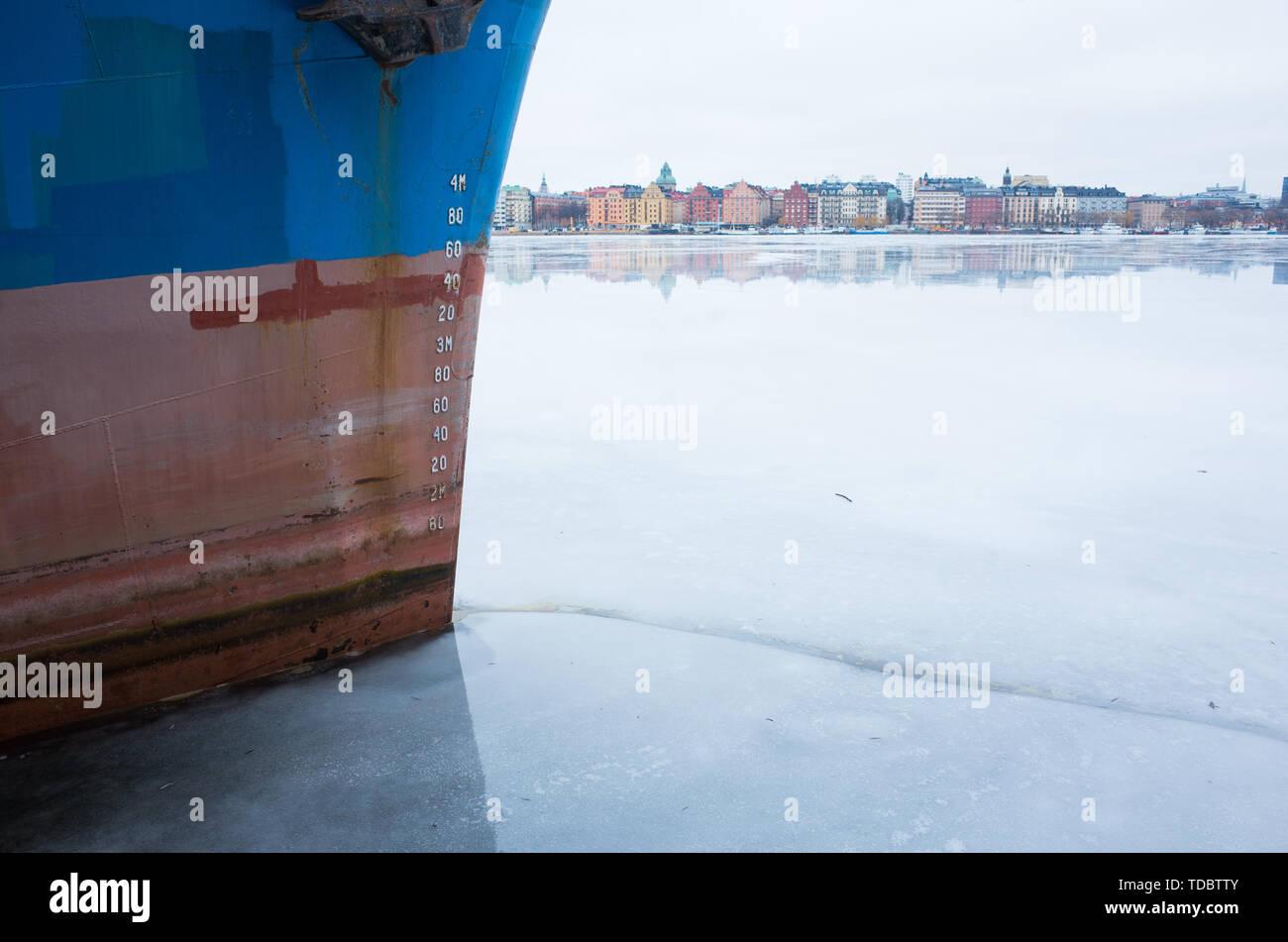 Vista invernal de Kungsholmen de Estocolmo, mirando a través del lago congelado con barcos amarrados en el primer plano. Foto de stock