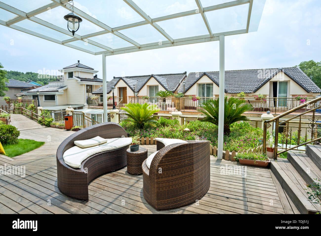Casa Patio Exterior Con Terraza De Madera Y Ratán Sofa Foto