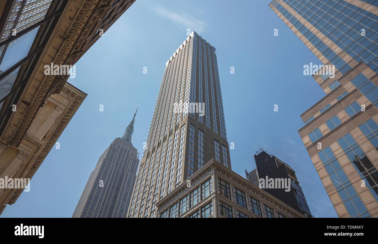 Nueva York, Manhattan, centro comercial. Rascacielos y el edificio Empire State, vista en perspectiva contra el cielo azul de fondo, vista de ángulo bajo, primavera sunn Foto de stock