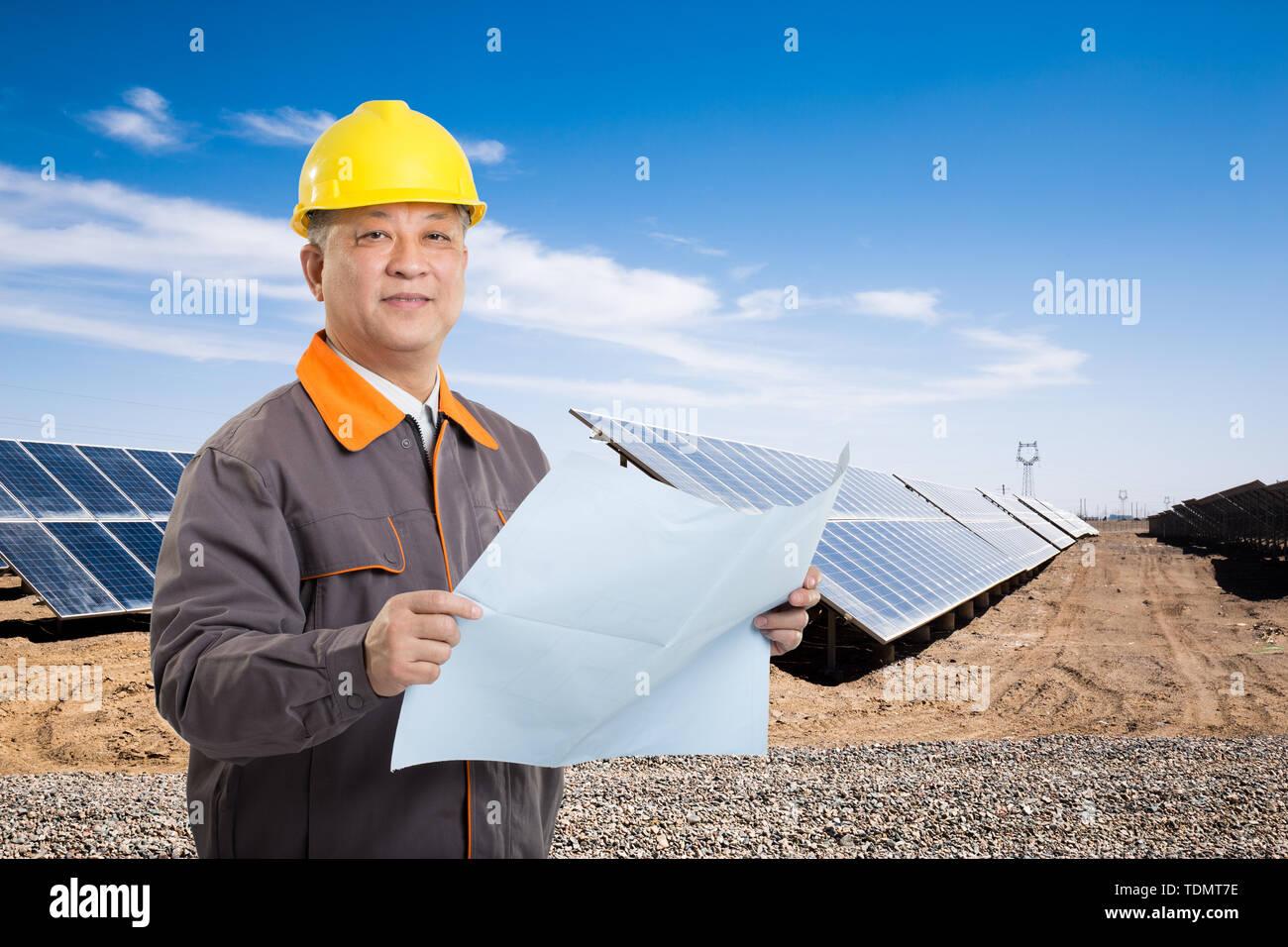 Hombre chino técnico con casco amarillo de pie delante de la planta solar en el país Imagen De Stock