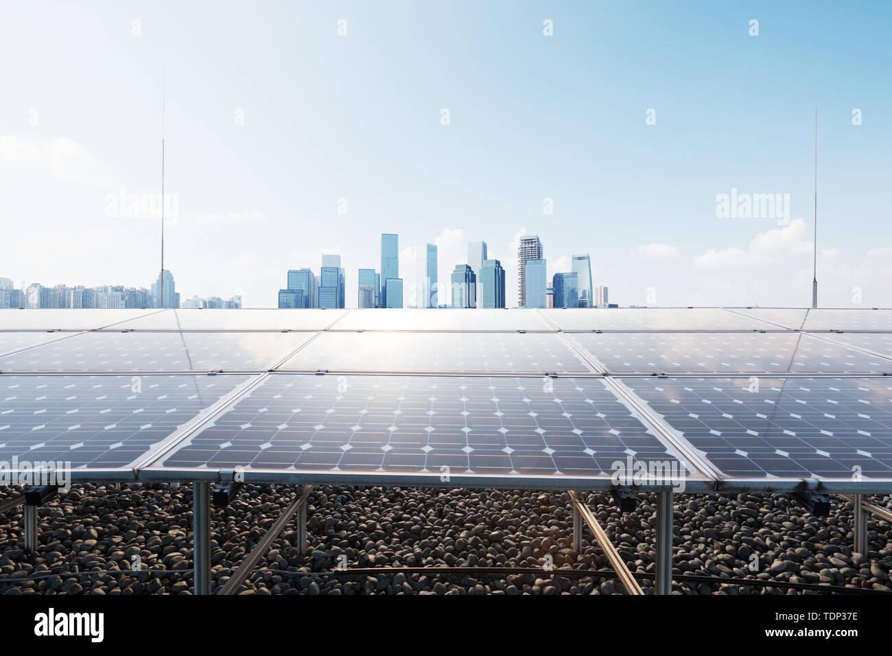 Los paneles solares con el paisaje urbano de la ciudad moderna Imagen De Stock