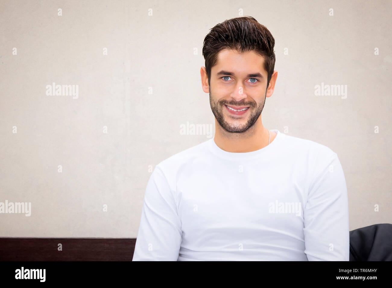 baa67a2e5 Joven hombre atractivo en una camiseta blanca en un sofá, retrato, Alemania  Imagen De
