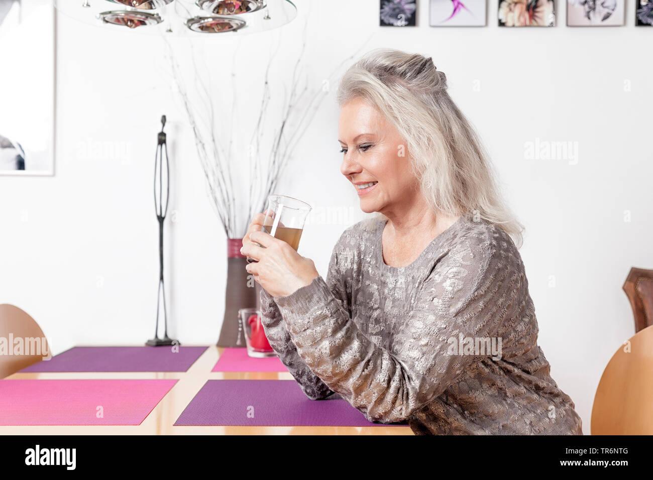 Contenido senior femenino sentado al escritorio y beber té, Alemania Imagen De Stock